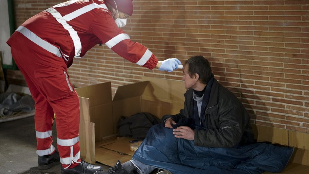 A red cross volunteer checks the temperature of a homeless man, in Rome, Wednesday, March 25, 2020. The new coronavirus causes mild or moderate symptoms for most people, but for some, especially older adults and people with existing health problems, it can cause more severe illness or death. (AP Photo/Andrew Medichin)