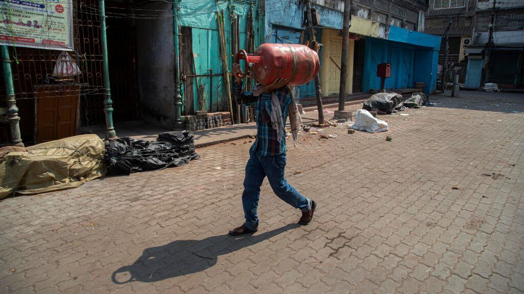 An Indian man walks carrying a cooking gas cylinder in Gauhati, India, Wednesday, March 25, 2020. (AP Photo/Anupam Nath)