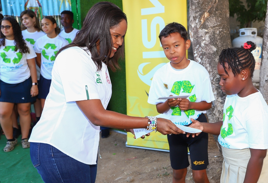 Environment Communication Officer at Wisynco, Shelly-Ann Dunkley (left) interacts with students at the American International School of Kingston's (AISK) during the ribbon cutting ceremony for the newly opened recycle cage.