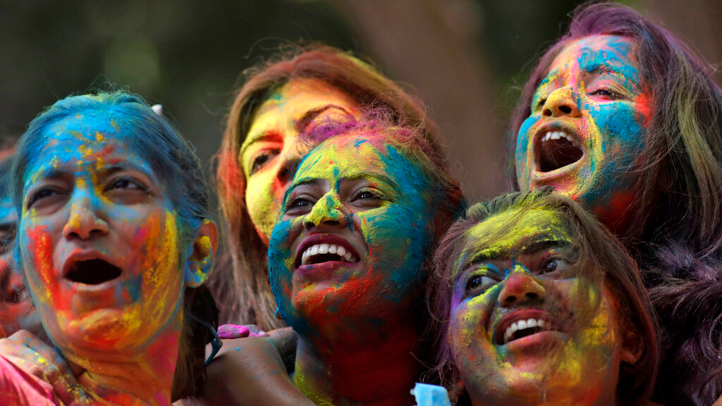 Women with their faces smeared with coloured powder cheer during celebrations marking the Holi festival in Mumbai, India, Tuesday, March 10, 2020. Holi, the festival of colours heralds the arrival of spring (AP Photo/Rajanish Kakade)