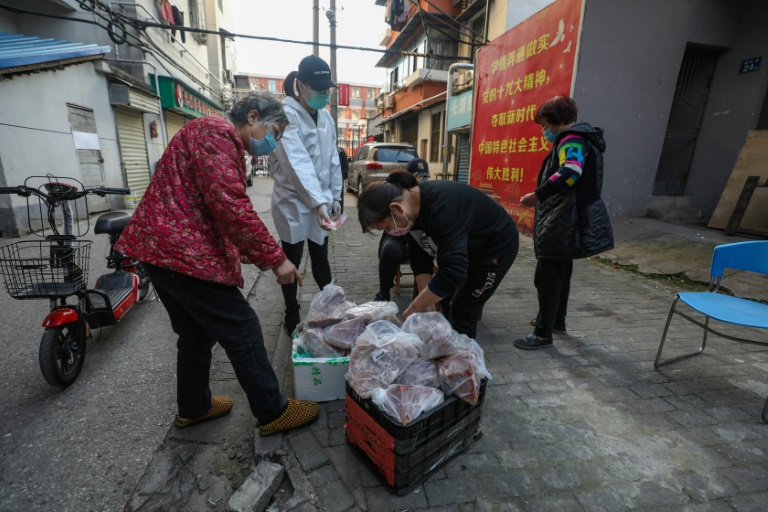 Des habitants récupèrent des paquets de viande de porc livrés dans leur quartier en quarantaine, le 18 mars 2020 à Wuhan, pendant l'épidémie du nouveau coronavirus. AFP / STR