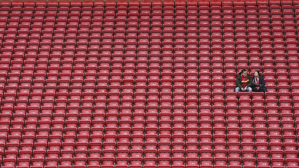 People sit surrounded by empty seats as they wait for the start of the English Premier League football match between Liverpool and Bournemouth at Anfield stadium in Liverpool, England, Saturday, March 7, 2020. (AP Photo/Jon Super)