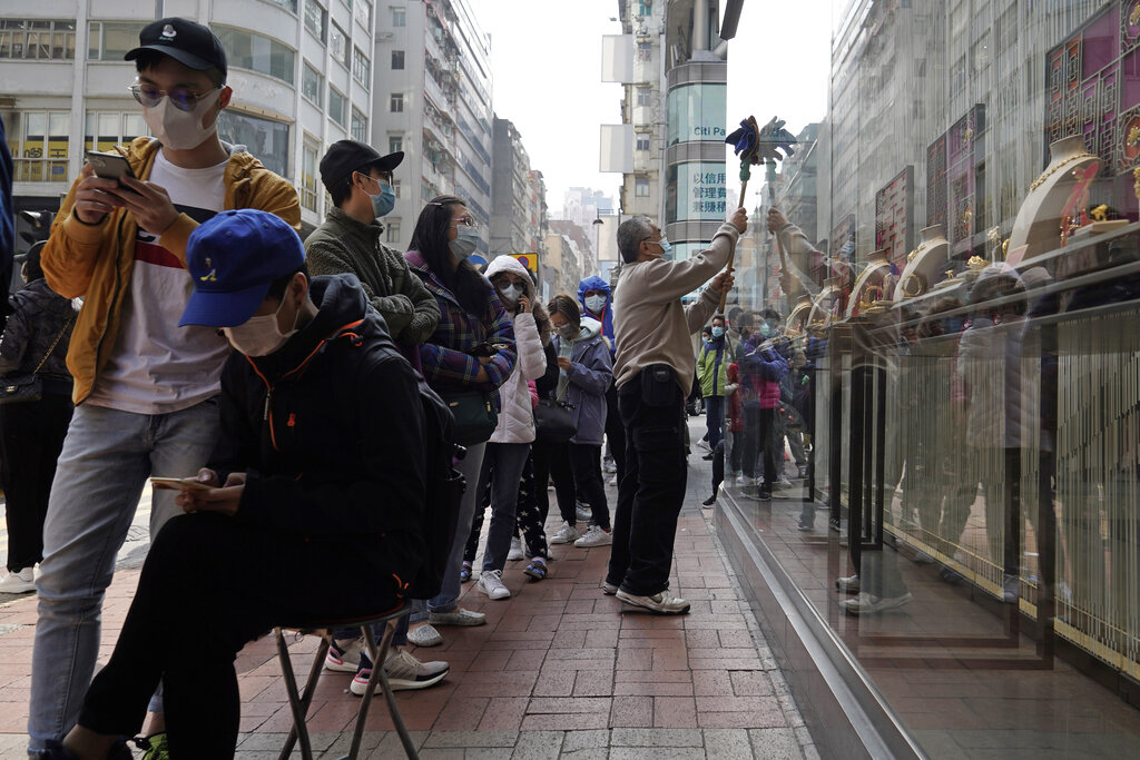 "A worker cleans a window of a jewelry shop as people queue up to buy face masks in Hong Kong, Saturday, Feb, 1, 2020. China's death toll from a new virus has risen over 250 and a World Health Organization official says other governments need to prepare for""domestic outbreak control"" if the disease spreads. (AP Photo/Kin Cheung)"