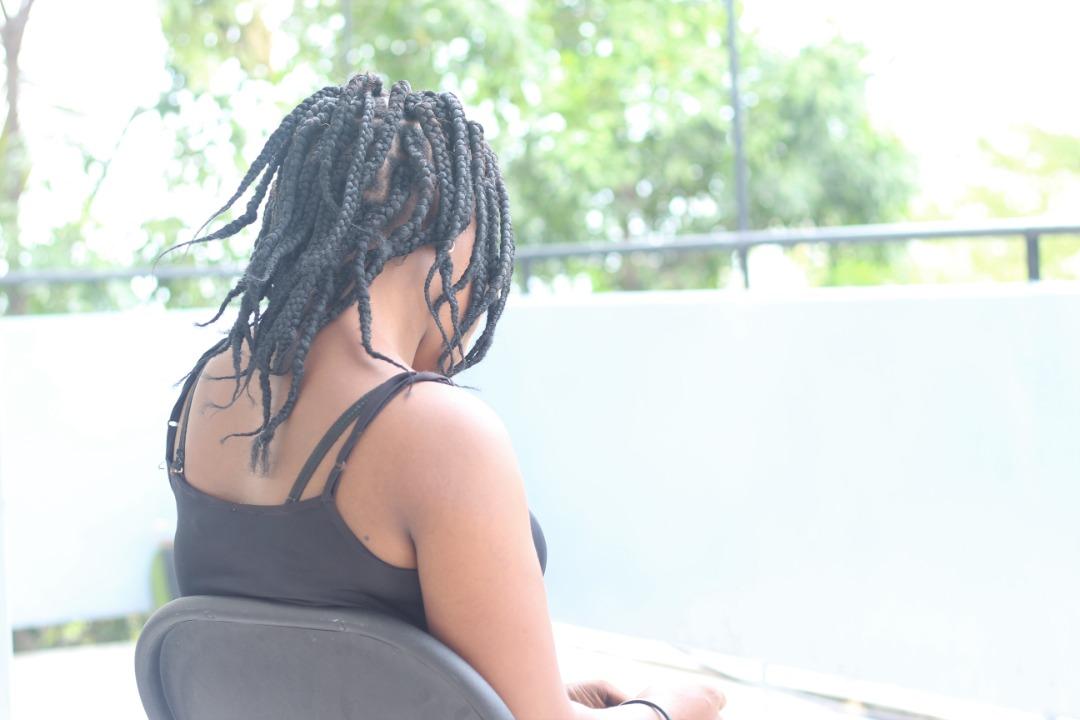 Une ancienne détenue et actrice de Gouyad Senpyè vue de dos. Photo: Eberline Nicolas/LoopHaïti