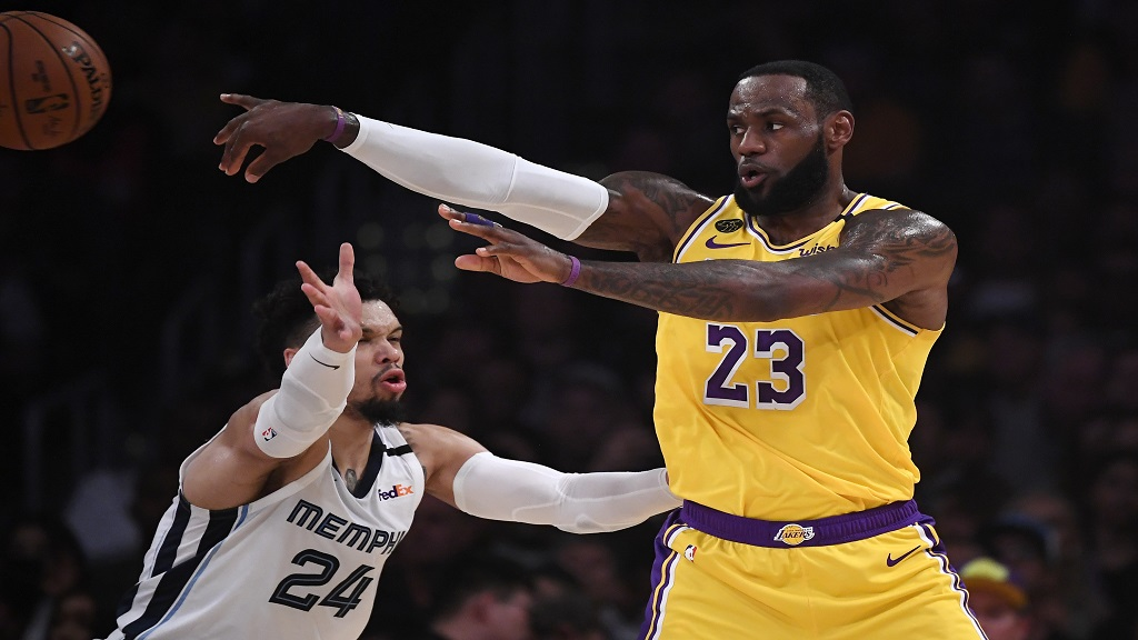 Los Angeles Lakers forward LeBron James, right, passes while under pressure from Memphis Grizzlies guard Dillon Brooks during the first half of an NBA basketball game Friday, Feb. 21, 2020, in Los Angeles. (AP Photo/Mark J. Terrill).