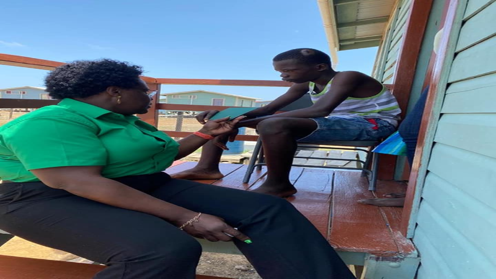 "Education Minister Simona Broomes speaking with 14 Year old Reon Mobb, who was injured while travelling on the ""David G"" school bus. Photo: Simona Broomes"