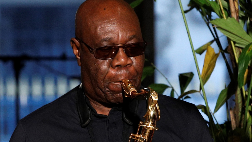 """is Jan.24, 2018 file photo, saxophonist Manu Dibango performs during Franck Sorbier's Haute Couture Spring-Summer 2018 fashion collection in Paris. Renowned jazz man Manu Dibango, to many the beloved """"Papy Groove"""" who served as an inspiration and pioneer in his art, died on Tuesday from the coronavirus, his official Facebook page announced. He was 86. For most people, the new coronavirus causes only mild or moderate symptoms. For some it can cause more severe illness. (AP Photo/Christophe Ena, File)"""