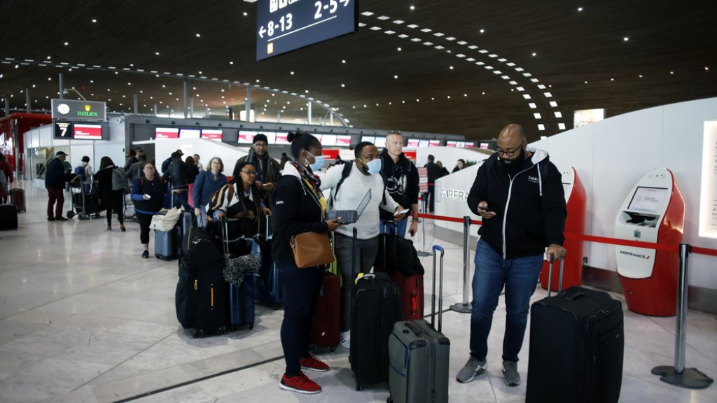 Passengers wait in front of the desk of Air France at the Roissy Charles de Gaulle airport, north of Paris, Thursday, March 12, 2020. The European Union on Thursday will evaluate President Donald Trump's decision to restrict travel from Europe to the United States amid deep concern over the economic impact of the move with markets already heavily hit by coronavirus. (AP Photo/Thibault Camus)