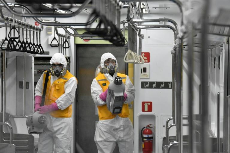Des employés en combinaison de protection désinfectent une rame du métro de Séoul en Corée du Sud, pour se prémunir du nouveau coronavirus, le 11 mars 2020
