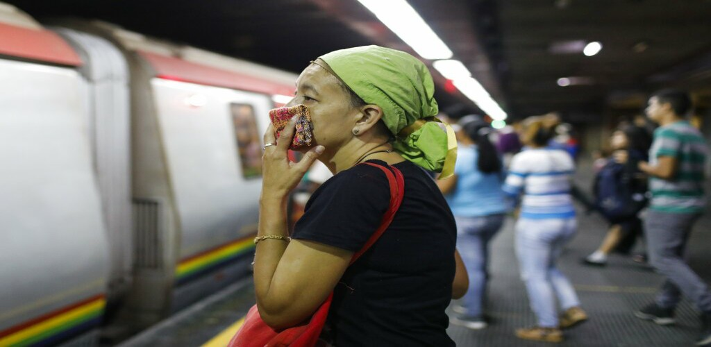 A woman covers her mouth and nose with a wash cloth on a subway platform in Caracas, Venezuela, Friday, March 13, 2020. Venezuela's Vice President Delcy Rodríguez confirmed Friday the first two cases of the new coronavirus in the South American country. The vast majority of people recover from the new virus. (AP Photo/Ariana Cubillos)