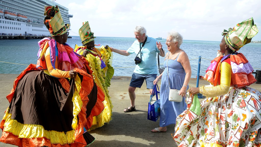 2.	Cultural dancers bedecked in traditional costume engage with cruise passengers at the Scarborough Port on March 8