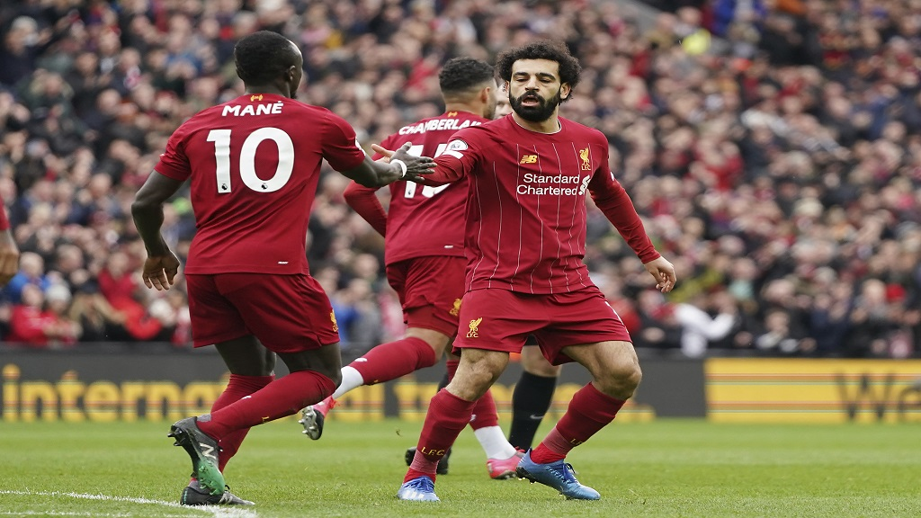 Liverpool's Mohamed Salah, right, celebrates with his teammate Sadio Mane after scoring his side's opening goal during the English Premier League football match against  Bournemouth at Anfield stadium in Liverpool, England, Saturday, March 7, 2020. (AP Photo/Jon Super).
