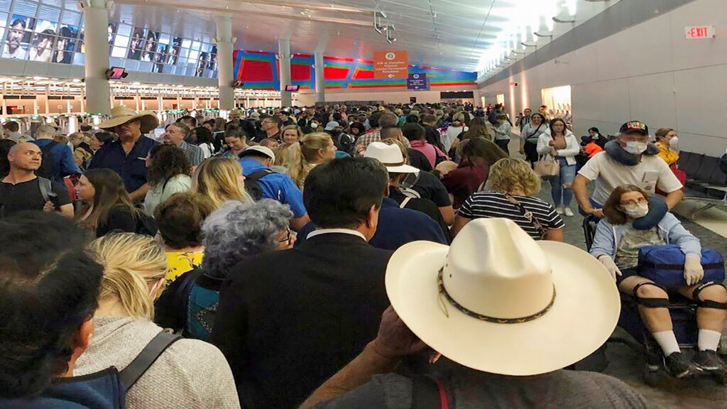 In this photo provided by Austin Boschen, people wait in line to go through the customs at Dallas Fort Worth International Airport in Grapevine, Texas, Saturday, March 14, 2020. (Austin Boschen via AP)