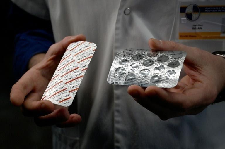 Un membre du personnel soignant de l'IHU Méditerranée Infection à Marseille montre deux plaquettes de médicaments: une de Nivaquine, qui contient de la chloroquine, et une de Plaqueril, qui contient de l'hydroxychloroquine, le 26 février 2020 afp.com - GERARD JULIEN