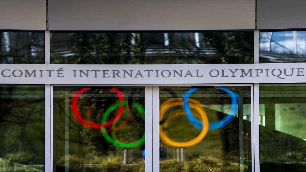 The Olympic Rings are displayed at the entrance of the IOC, International Olympic Committee headquarters during the coronavirus disease (COVID-19) outbreak in Lausanne, Switzerland, Tuesday, March 24, 2020. (Jean-Christophe Bott/Keystone via AP).