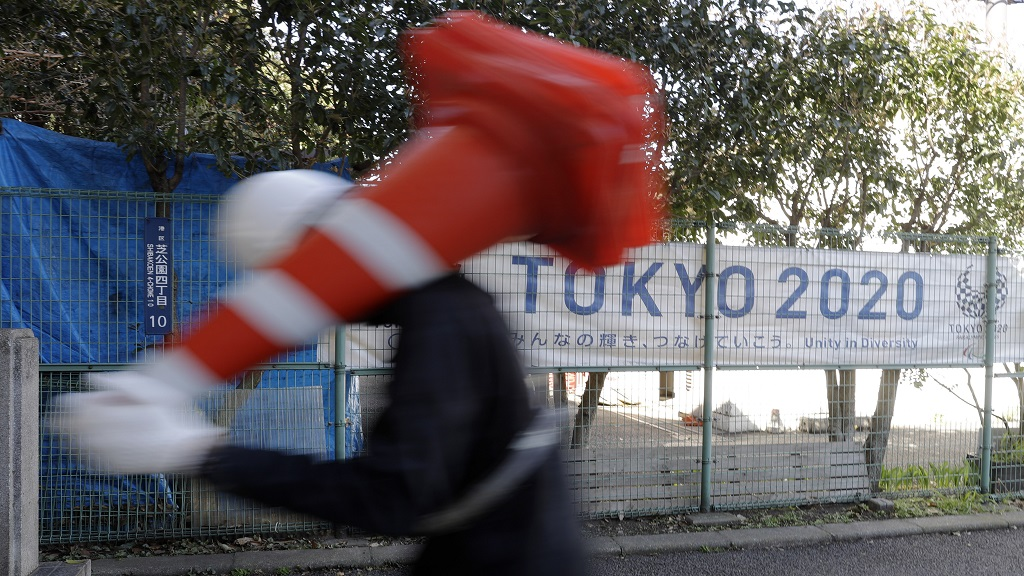 A worker on duty at a road construction site walks past a banner promoting the 2020 Olympic Games in Tokyo, Friday, March 20, 2020. The Olympic flame from Greece arrived in Japan even as the opening of the the Tokyo Games in four months is in doubt with more voices suggesting the games should to be postponed or cancelled because of the worldwide virus pandemic. (AP Photo/Gregorio Borgia).