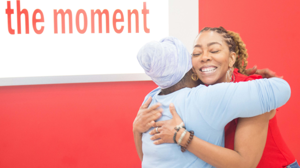 Penny Gomez, Digicel Foundation CEO hugs Joan R after presenting her with a return ticket to Dominica to attend her Grandson's wedding.