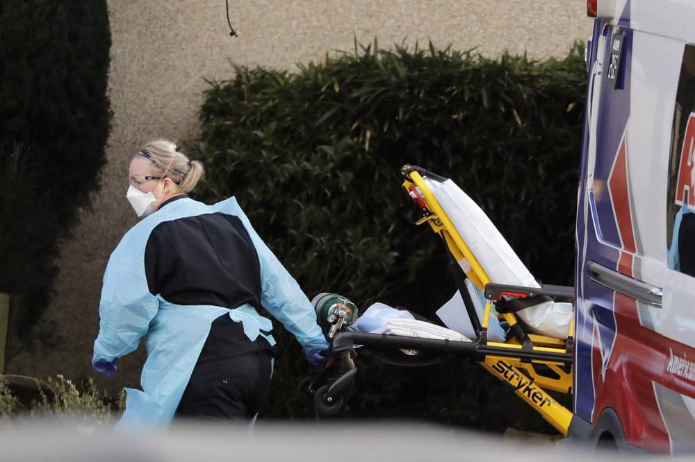 An ambulance worker wears protective equipment as she wheels a stretcher into a nursing facility where more than 50 people are sick and being tested for the COVID-19 virus, Saturday, February 29, 2020, in Kirkland, Washington. Neither patient travelled out of the country. (AP Photo/Elaine Thompson)