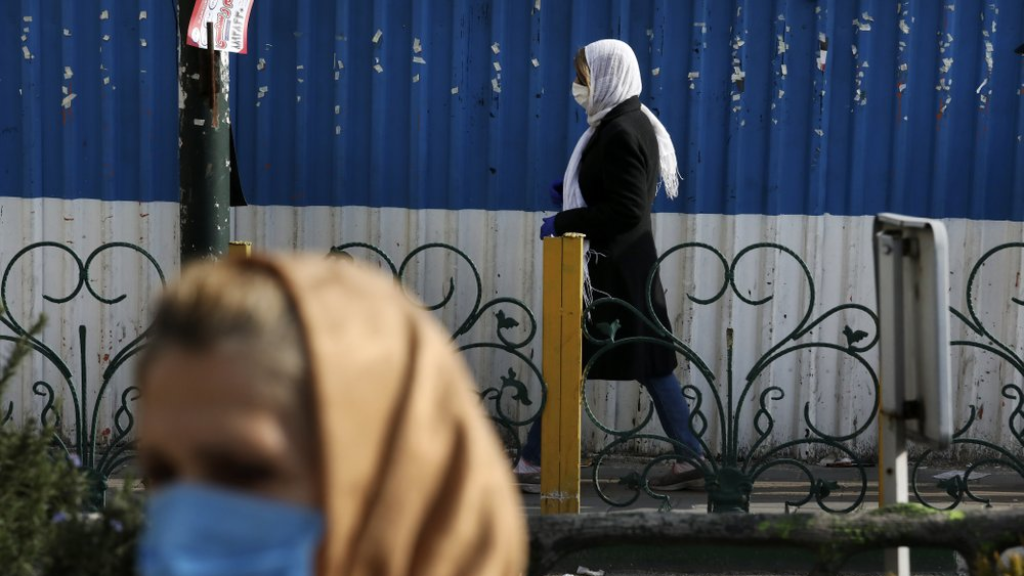Pedestrians wearing face masks walk on the sidewalks in northern Tehran, Iran, Sunday, March 1, 2020. While the new coronavirus has extended its reach across the world, geographic clusters of infections were emerging, with Iran, Italy and South Korea seeing rising cases. (AP Photo/Vahid Salemi)