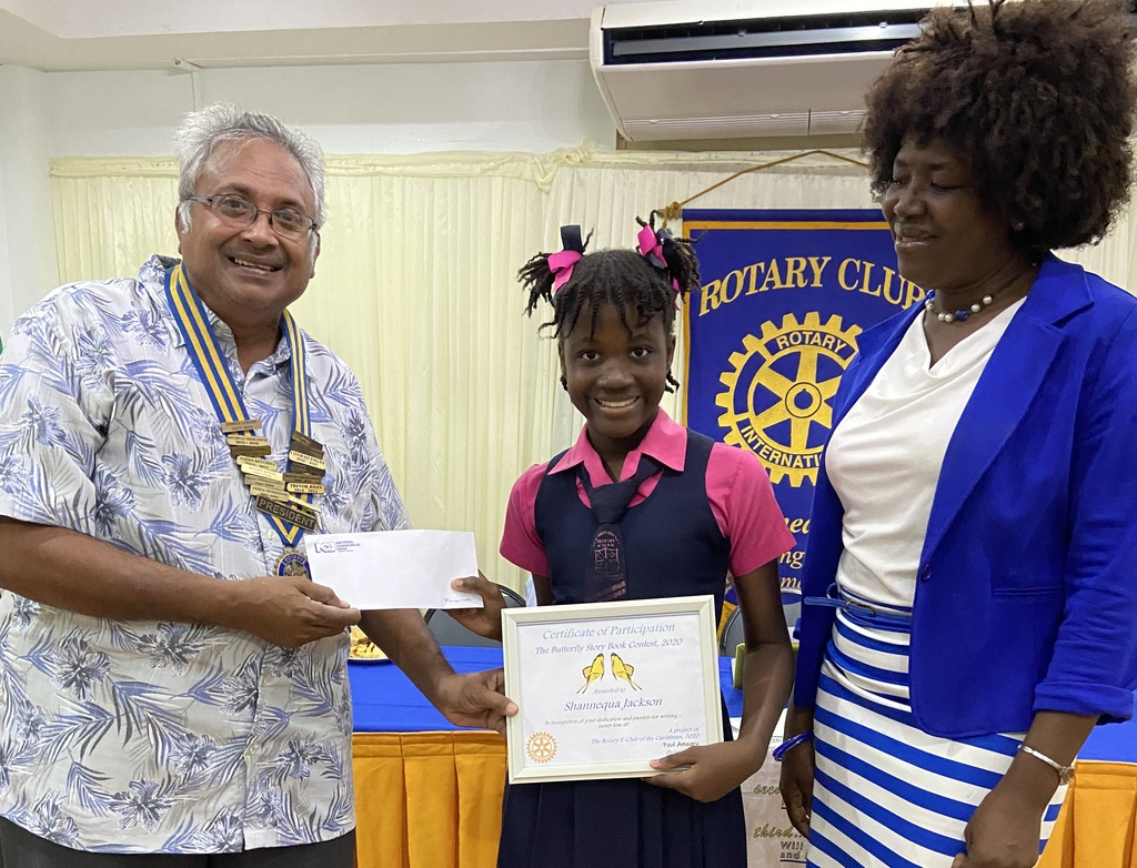 [L-r] Sydney Lowrie, President of the Rotary Club of Liguanea Plains presents 10 year old Shannequa Jackson of New Providence Primary School with her certificate and cheque for winning the Caribbean-wide 'Butterfly Storybook Project'. By her side is the school's Principal, Olga Clarke.