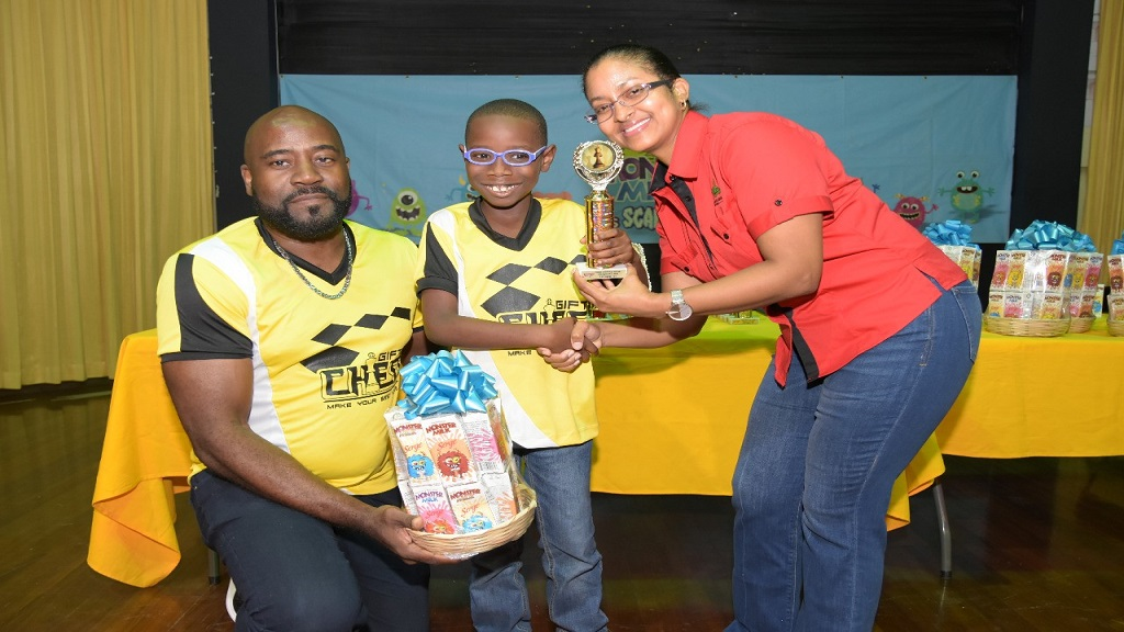 Seven-year-old Khaleel Johnson Bartlett (centre) is presented with his prize for emerging champion of the Under-8 category at the National Age Group Chess Championship, which was held at the University of Technology (UTech) Auditorium recently. Presenting Khaleel with his prize is Dr Camille Edwards-McKennis (right), Chairman of the Junior Chess Committee, Jamaica Chess Federation, while his coach, Adrian Palmer, helps in collecting the winnings.