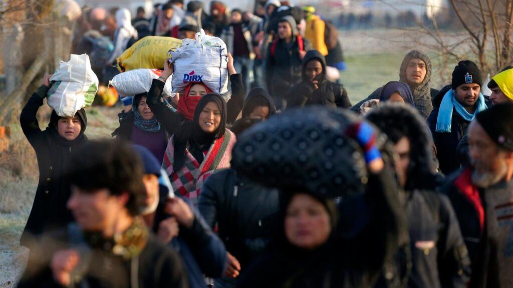 Migrants walk to reach Pazarakule border gate, Edirne, Turkey, at the Turkish-Greek border on Sunday, March 1, 2020. (AP Photo/Emre Tazegul)