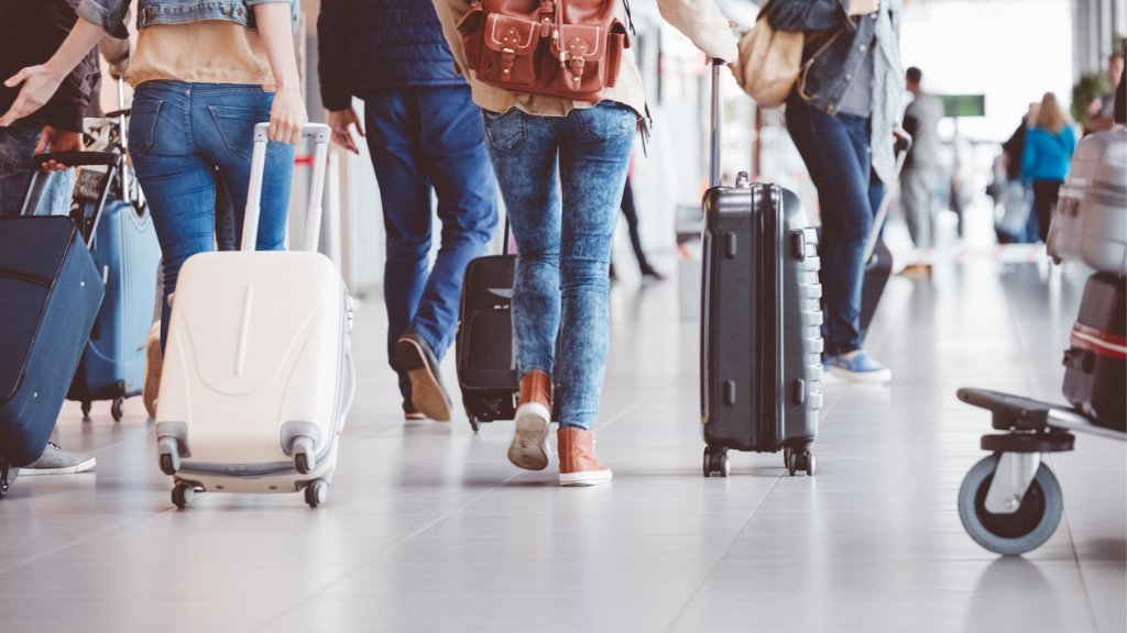 Stock photo of passengers walking in an airport terminal.