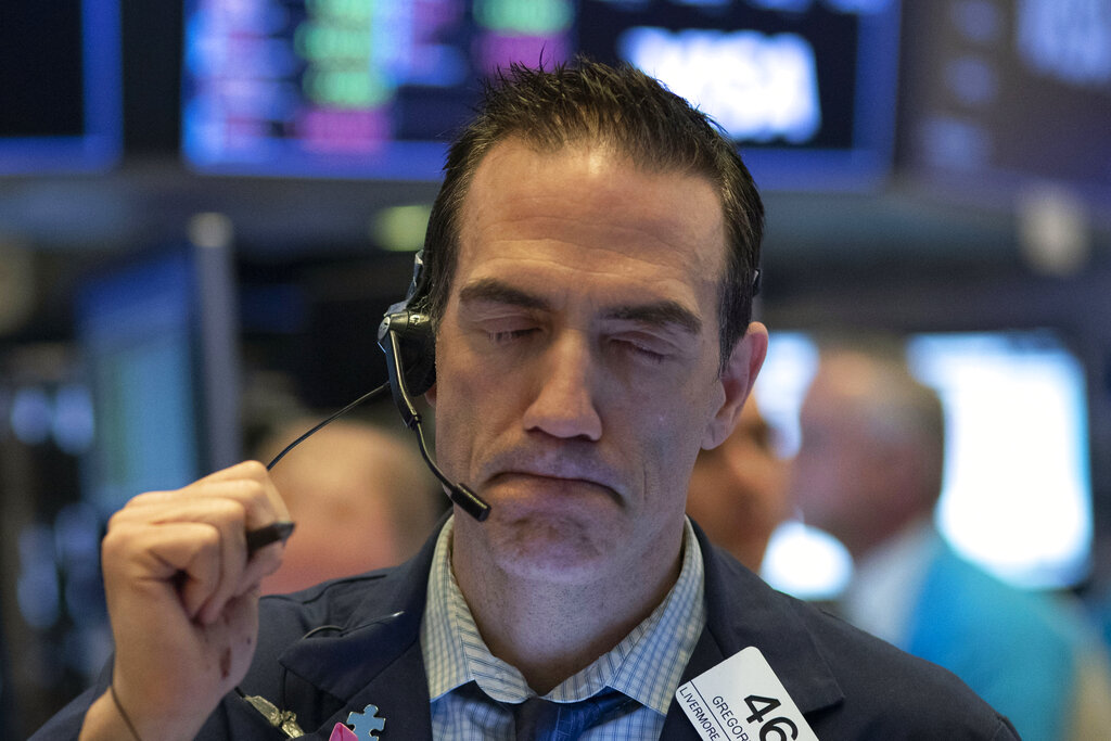 Stock trader Gregory Rowe works at the New York Stock Exchange, Wednesday, March 18, 2020 in New York.
