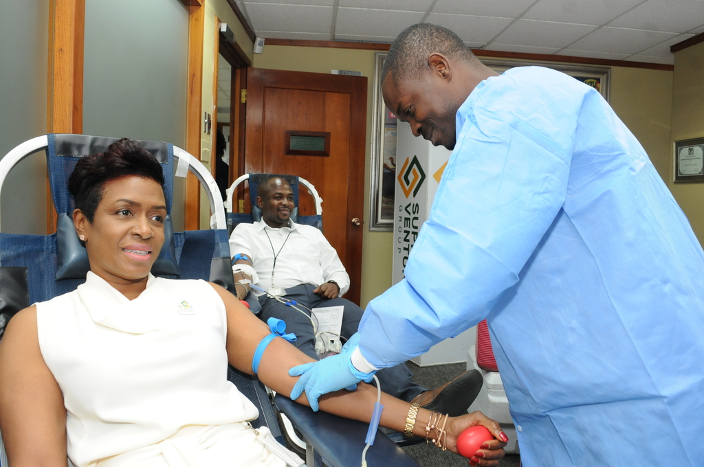 Supreme Ventures Group President and CEO, Ann-Dawn Young Sang braces for the injection to start her donation to the Corporate Blood Drive at its New Kingston office.