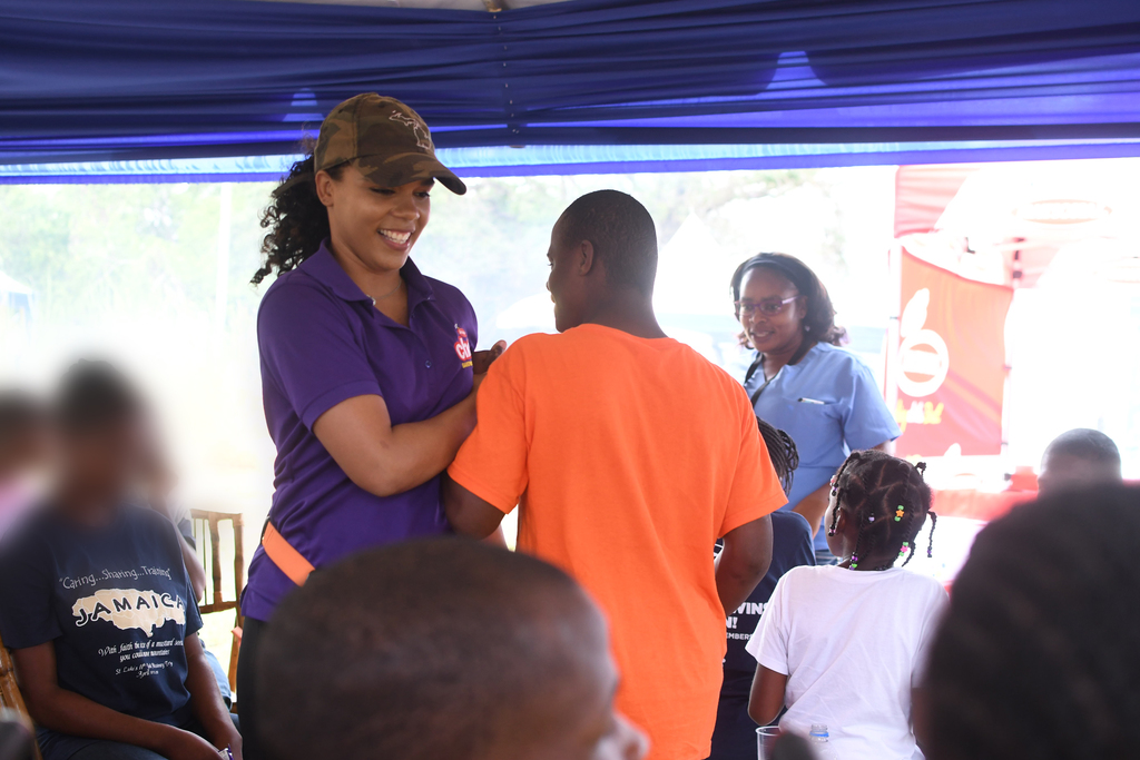 "MC of the Kids' Village, Soyini Phillips, delights in a game of ""Ring a Ring o' Roses"" with the kids."