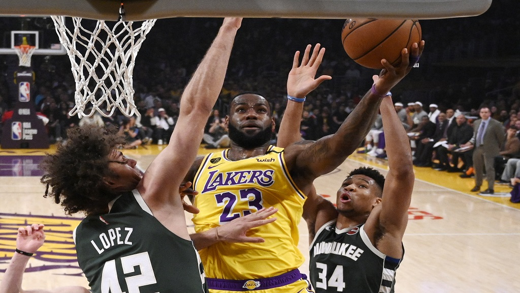 Los Angeles Lakers forward LeBron James, center, shoots as Milwaukee Bucks center Robin Lopez, left, and forward Giannis Antetokounmpo defend during the first half of an NBA basketball game Friday, March 6, 2020, in Los Angeles. (AP Photo/Mark J. Terrill).