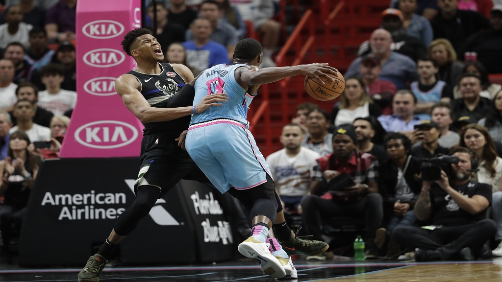 Miami Heat forward Bam Adebayo (13) fouls Milwaukee Bucks forward Giannis Antetokounmpo while going to shoot during the second half of an NBA basketball game, Monday, March 2, 2020, in Miami. (AP Photo/Wilfredo Lee).