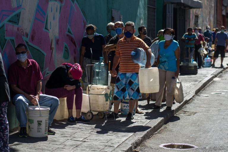 Des habitants de Caracas attendent pour remplir leurs bidons d'eau le 27 mars 2020