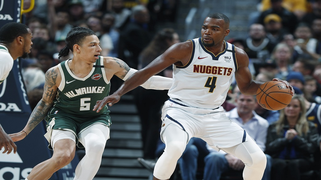 Denver Nuggets forward Paul Millsap, right, works the ball to the basket as Milwaukee Bucks forward D.J. Wilson defends in the second half of an NBA basketball game Monday, March 9, 2020, in Denver. (AP Photo/David Zalubowski).