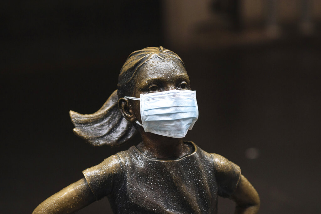 """A surgical mask is placed on The """"Fearless Girl"""" statue outside the New York Stock Exchange on Thursday, March 19, 2020, in New York. Stocks are swinging between gains and losses in early trading on Wall Street Thursday, but the moves are more subdued than the wild jabs that have dominated recent weeks. (AP Photo/Kevin Hagen)"""
