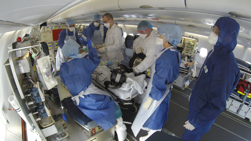 This GoPro image provided Saturday March 28, 2020 by the French Army shows doctors taking care of evacuated patients infected with the Covid-19 disease, aboard a military plane from Mulhouse, eastern France to Bordeaux, southwestern France, Friday March 27, 2020. France is evacuating its citizens infected with the coronavirus in Eastern France.