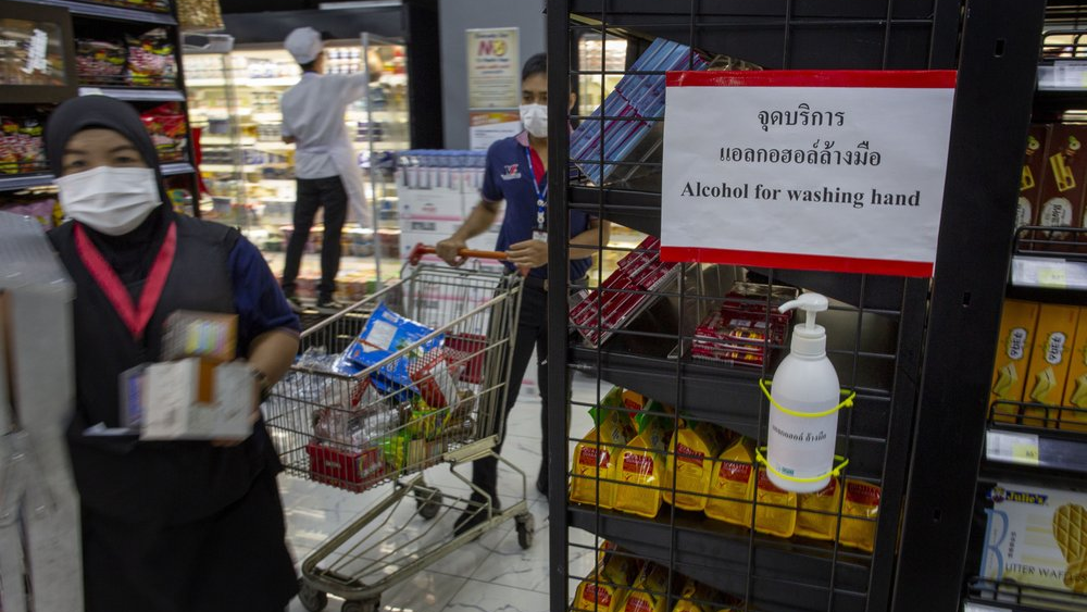 A hand sanitizer container is mounted in store-shelf as staff with face masks place supplies in a supermarket in Bangkok, Thailand, Tuesday, March 24, 2020. Most popular shopping malls remained shut in Bangkok, except supermarkets and pharmacies to combat the spread of new coronavirus. For most people, the new coronavirus causes only mild or moderate symptoms. For some, especially older adults it can cause more severe illness. (AP Photo/Gemunu Amarasinghe)