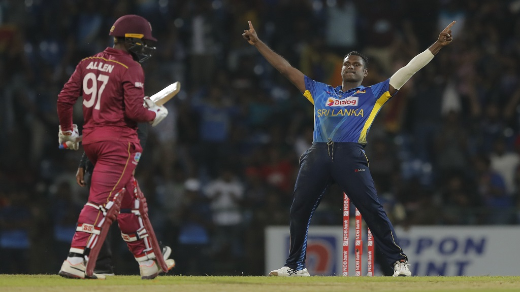 Sri Lanka's Angelo Mathews celebrates the dismissal of West Indies' Fabian Allen, left, during their third one day international cricket match in Pallekele, Sri Lanka, Sunday, March 1, 2020. (AP Photo/Eranga Jayawardena)