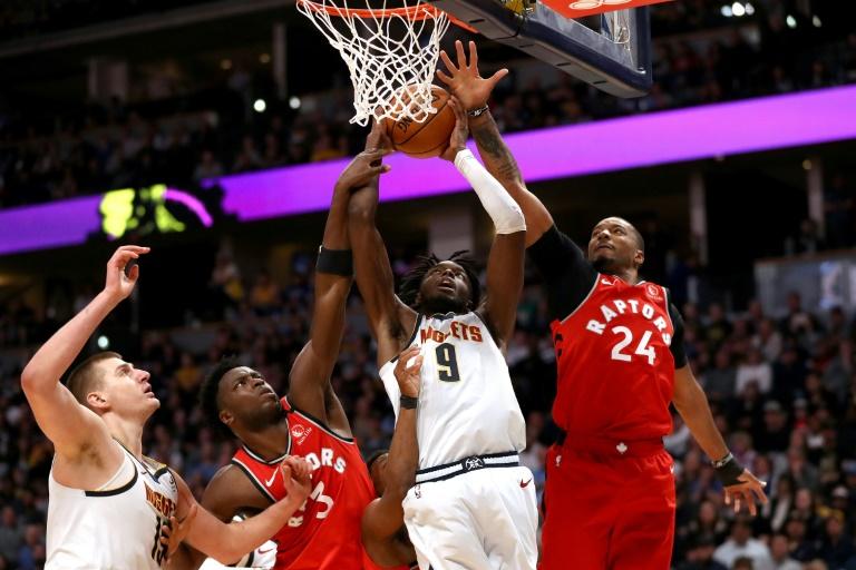 Jerami Grant, joueur des Denver Nuggets, tente de marquer un panier contre OG Anunoby et Norman Powell lors du match de NBA face aux Toronto Raptors le 1er mars 2020 à Denver (Etats-Unis)