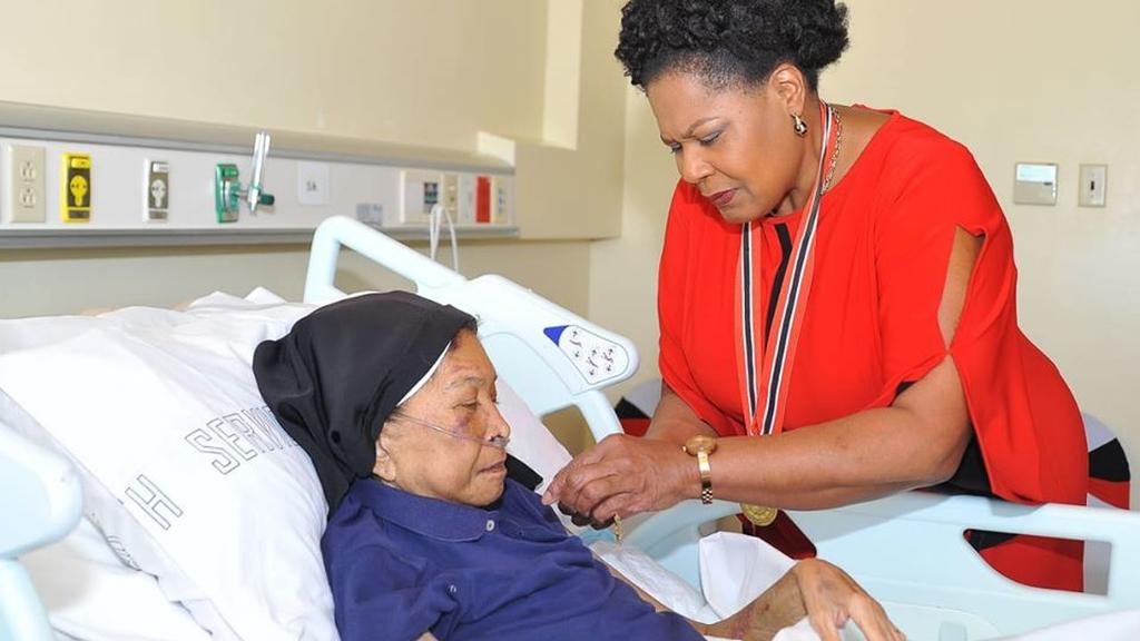 Sister Phyllis receiving her Medal of Merit from President Paula Mae Weekes in September