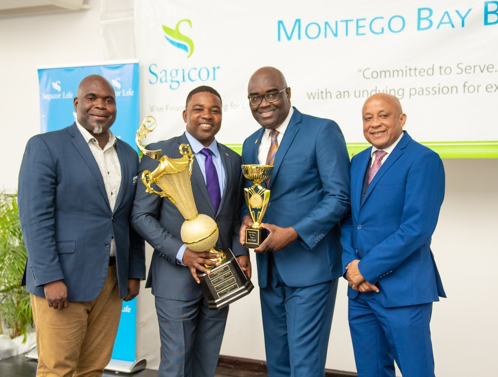 Philbert Perry (left), assistant vice president, Sagicor Life Jamaica, Individual Life Division; and Mark Chisholm, executive vice president, Sagicor Life Jamaica, congratulate top financial advisors from the Montego Bay branch Oneil Brown (2nd left) and Dean Miller, following the branch's awards ceremony.