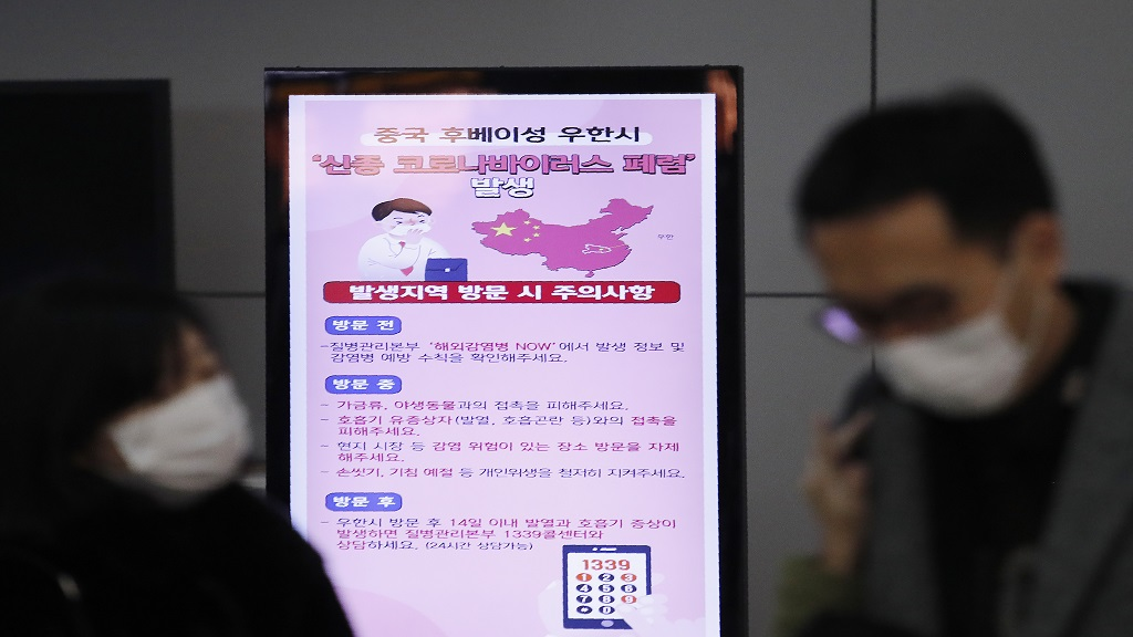 In this Monday, January 27, 2020, file photo, a poster warning about coronavirus is seen as passengers wear masks in a departure lobby at Incheon International Airport in Incheon, South Korea. (Photo: AP)
