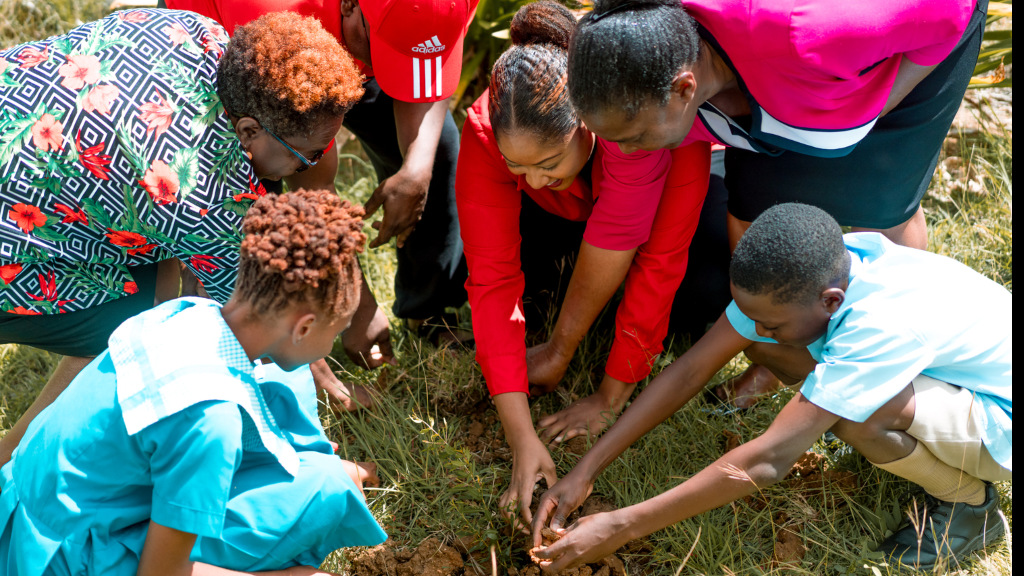 Members of Digicel Team with Students from Holy Innocents Primary and St. Thomas Committee, planting trees for the million trees initiative