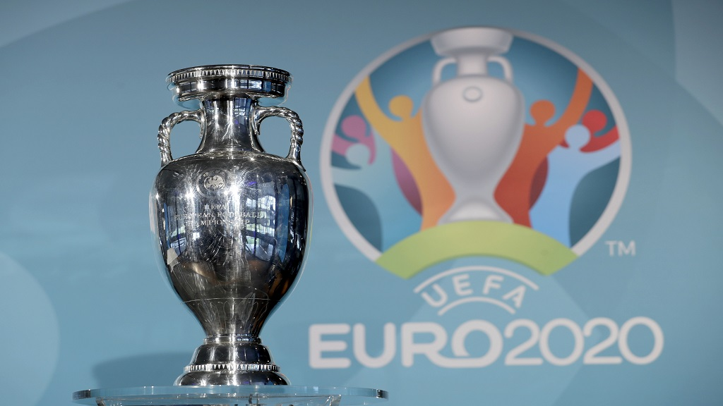 In this Thursday, Oct. 27, 2016 file photo the Euro football championships trophy is seen in front of the logo during the presentation of Munich's logo as one of the host cities of the Euro 2020 European football championships in Munich, Germany. (AP Photo/Matthias Schrader, File).