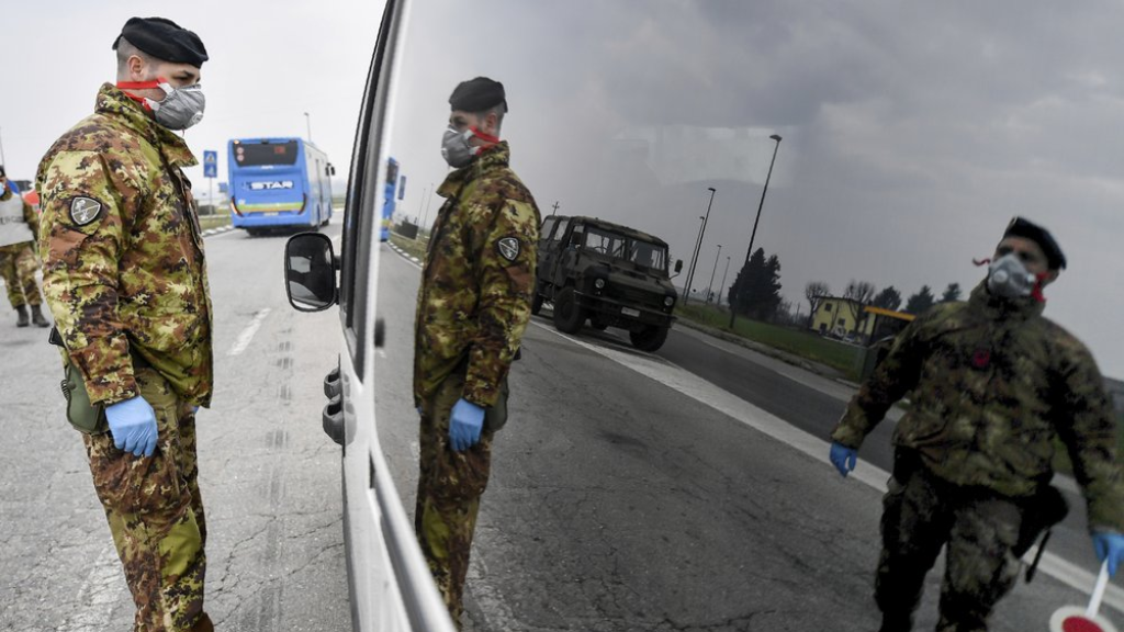 Italian Army soldiers check transit to and from the cordoned areas near Turano Lodigiano, Northern Italy, Tuesday, Feb. 25, 2020. Civil protection officials on Tuesday reported a large jump of cases in Italy, from 222 to 283. Seven people have died, all of them elderly people suffering other pathologies. (Claudio Furlan/Lapresse via AP)
