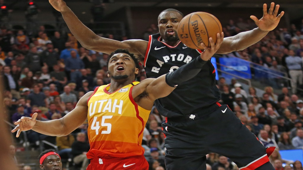 Toronto Raptors center Serge Ibaka, rear, defends against Utah Jazz guard Donovan Mitchell (45) who goes to the basket in the second half during an NBA basketball game Monday, March 9, 2020, in Salt Lake City. (AP Photo/Rick Bowmer).