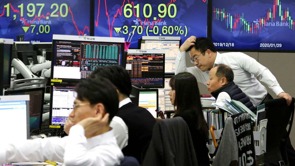 Currency traders watch monitors at the foreign exchange dealing room of the KEB Hana Bank headquarters in Seoul, South Korea, Tuesday, March 10, 2020. (AP Photo/Ahn Young-joon)