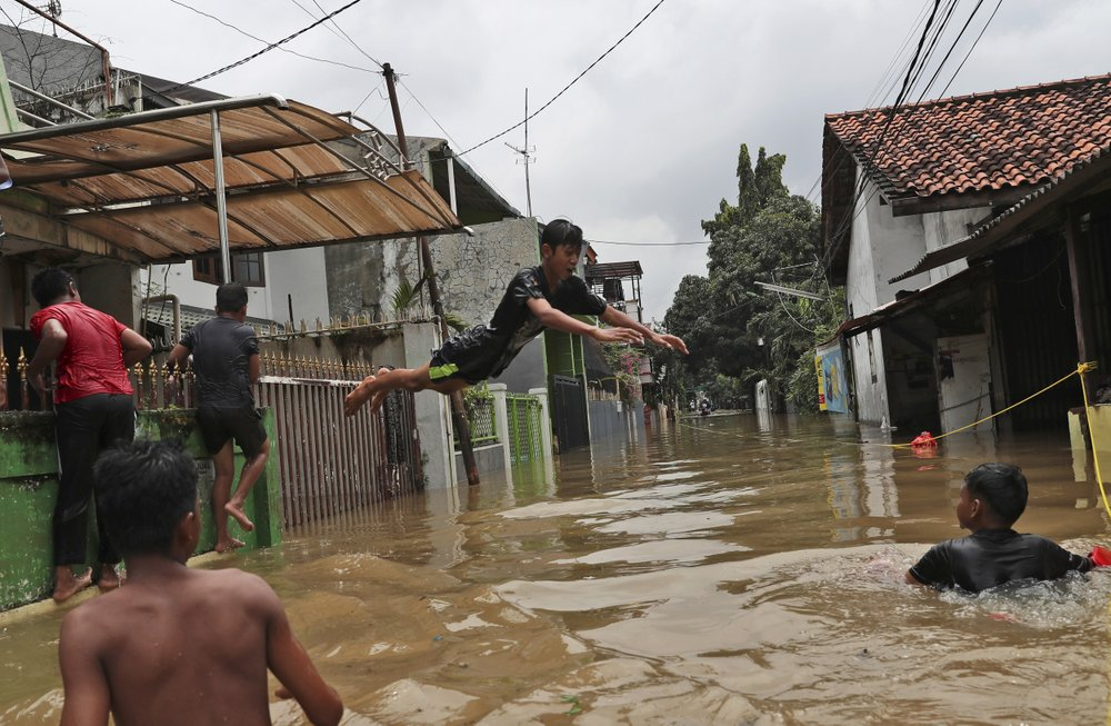 Indonesian youths play in flood water in a neighborhood in Jakarta, Indonesia, Tuesday, Feb. 25, 2020. Overnight rains caused rivers to burst their banks in greater Jakarta sending muddy water into residential and commercial areas, inundating thousands of homes and paralyzing parts of the city's transport networks, officials said. (AP Photo/Achmad Ibrahim)