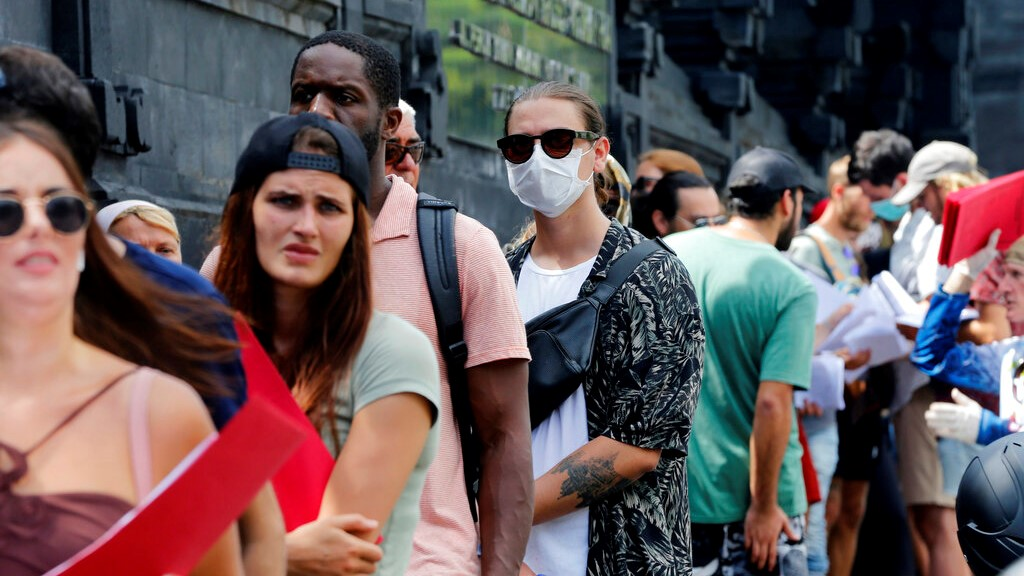 In this March 23, 2020 photo, foreign tourists who are unable to fly home due to the new coronavirus outbreak, queue up outside an immigration office to extend their visas in Bali, Indonesia. (AP Photo/Firdia Lisnawati)