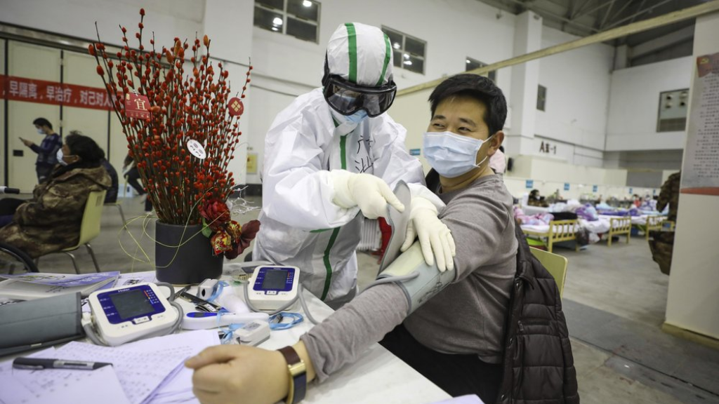 In this February 18, 2020, photo, a medical staff member attends to a COVID-19 patient in a temporary hospital converted from an exhibition center in Wuhan in central China's Hubei province. The hospital, one of the dozen of its kind built in Wuhan, hosts COVID-19 patients with mild symptoms. (Chinatopix Via AP) CHINA OUT)